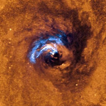 La imagen muestra el proceso de alimentación nuclear de un agujero negro en la galaxia NGC 1566 y cómo los filamentos de polvo que envuelven el núcleo activo quedan atrapados y giran alrededor del agujero negro hasta que son tragados por él. Crédito: ESO.